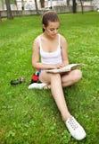 Chica joven hermosa que lee el libro Imagenes de archivo