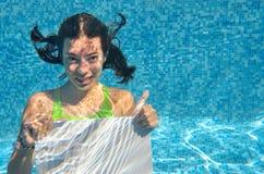 Chica joven hermosa que lleva a cabo el tablero en blanco blanco en piscina debajo del agua, vacaciones de familia Imagenes de archivo