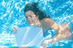 Chica joven hermosa que lleva a cabo el tablero en blanco blanco en piscina debajo del agua, diversión el vacaciones de familia Imagen de archivo libre de regalías