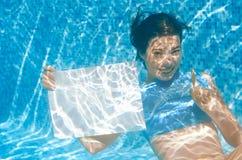Chica joven hermosa que lleva a cabo el tablero en blanco blanco en piscina debajo del agua, diversión el vacaciones de familia Imagenes de archivo