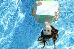 Chica joven hermosa que lleva a cabo el tablero en blanco blanco en piscina debajo del agua, diversión el vacaciones de familia Imagen de archivo