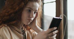 Chica joven hermosa que manda un SMS de smartphone almacen de metraje de vídeo