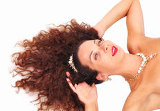 Chica joven hermosa que miente con su pelo en un fondo blanco Foto de archivo libre de regalías