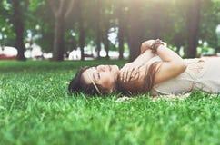 Chica joven hermosa que miente en hierba en parque del verano Imagen de archivo libre de regalías