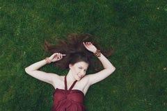Chica joven hermosa que miente en hierba en parque del verano Fotografía de archivo
