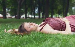 Chica joven hermosa que miente en hierba en parque del verano Imagenes de archivo