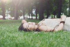 Chica joven hermosa que miente en hierba en parque del verano Foto de archivo