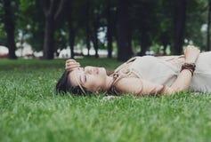 Chica joven hermosa que miente en hierba en parque del verano Fotografía de archivo libre de regalías