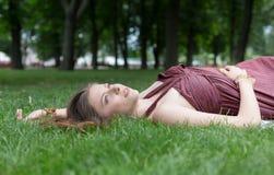 Chica joven hermosa que miente en hierba en parque del verano Fotos de archivo