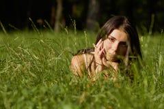 Chica joven hermosa que miente en hierba verde Fotos de archivo