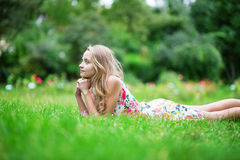 Chica joven hermosa que miente en la hierba Fotos de archivo