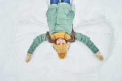 Chica joven hermosa que miente en la nieve Fabricación de un ángel de la nieve Fotos de archivo libres de regalías