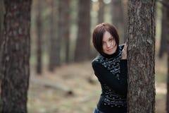Chica joven hermosa que mira a escondidas de detrás un tronco del pino Imagen de archivo