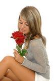 Chica joven hermosa que mira la rosa del rojo Fotos de archivo