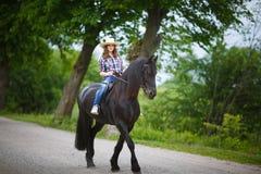 Chica joven hermosa que monta un caballo en campo Fotos de archivo