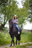 Chica joven hermosa que monta un caballo en campo Imagenes de archivo
