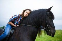 Chica joven hermosa que monta un caballo en campo Fotografía de archivo