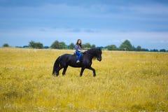 Chica joven hermosa que monta un caballo en campo Imágenes de archivo libres de regalías