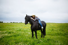 Chica joven hermosa que monta un caballo en campo Foto de archivo libre de regalías