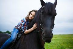 Chica joven hermosa que monta un caballo en campo Fotos de archivo libres de regalías