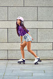 Chica joven hermosa que patina en pcteres de ruedas Imágenes de archivo libres de regalías