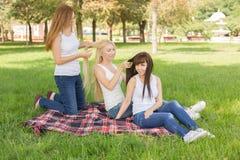 Chica joven hermosa que plantea sentarse en la tela escocesa en el parque Foto de archivo libre de regalías
