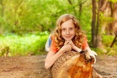 Chica joven hermosa que pone en el bosque del inicio de sesión Foto de archivo libre de regalías