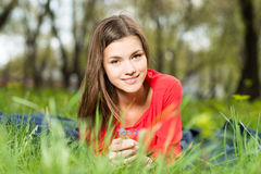 Chica joven hermosa que pone en parque Imagen de archivo libre de regalías