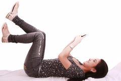 Chica joven hermosa que pone en una charla de la almohadilla Imagen de archivo libre de regalías