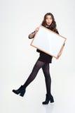 Chica joven hermosa que presenta con el tablero en blanco Imagenes de archivo