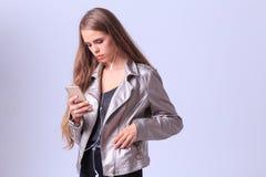 Chica joven hermosa que presenta en estudio en un fondo gris Imagen de archivo