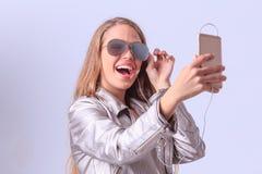 Chica joven hermosa que presenta en estudio en un fondo gris Imagen de archivo libre de regalías
