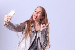 Chica joven hermosa que presenta en estudio en un fondo gris Imágenes de archivo libres de regalías