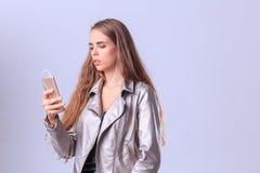 Chica joven hermosa que presenta en estudio en un fondo gris Foto de archivo