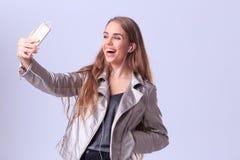 Chica joven hermosa que presenta en estudio en un fondo gris Fotografía de archivo