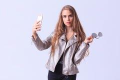 Chica joven hermosa que presenta en estudio en un fondo gris Fotos de archivo