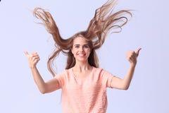 Chica joven hermosa que presenta en estudio en un fondo gris Imagenes de archivo