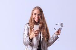 Chica joven hermosa que presenta en estudio en un fondo gris Fotos de archivo libres de regalías