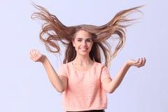 Chica joven hermosa que presenta en estudio en un fondo gris Foto de archivo libre de regalías