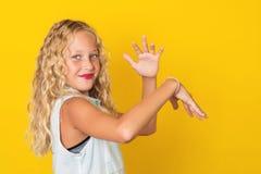 Chica joven hermosa que presenta en fondo amarillo Imagenes de archivo