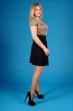 Chica joven hermosa que presenta en un fondo azul Imagen de archivo libre de regalías
