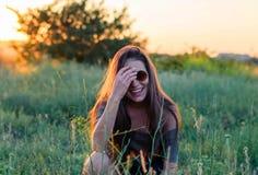 Chica joven hermosa que ríe en gafas de sol redondas en la luz de la puesta del sol Imagenes de archivo