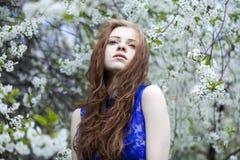 Chica joven hermosa que se coloca cerca de árboles florecientes en la primavera Gard Imágenes de archivo libres de regalías