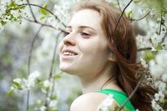 Chica joven hermosa que se coloca cerca de árboles florecientes en la primavera Gard Foto de archivo libre de regalías