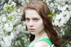 Chica joven hermosa que se coloca cerca de árboles florecientes en la primavera Gard Fotos de archivo