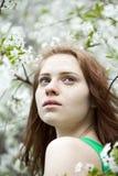 Chica joven hermosa que se coloca cerca de árboles florecientes en la primavera Gard Imagenes de archivo