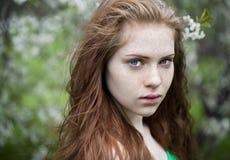 Chica joven hermosa que se coloca cerca de árboles florecientes en la primavera Gard Imagen de archivo libre de regalías