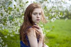 Chica joven hermosa que se coloca cerca de árboles florecientes en la primavera Gard Foto de archivo