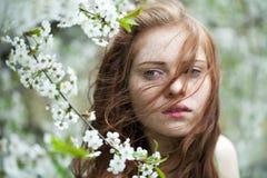 Chica joven hermosa que se coloca cerca de árboles florecientes en la primavera Gard Fotografía de archivo libre de regalías