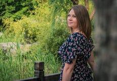 Chica joven hermosa que se coloca en el puente de madera en parque verde Fotografía de archivo